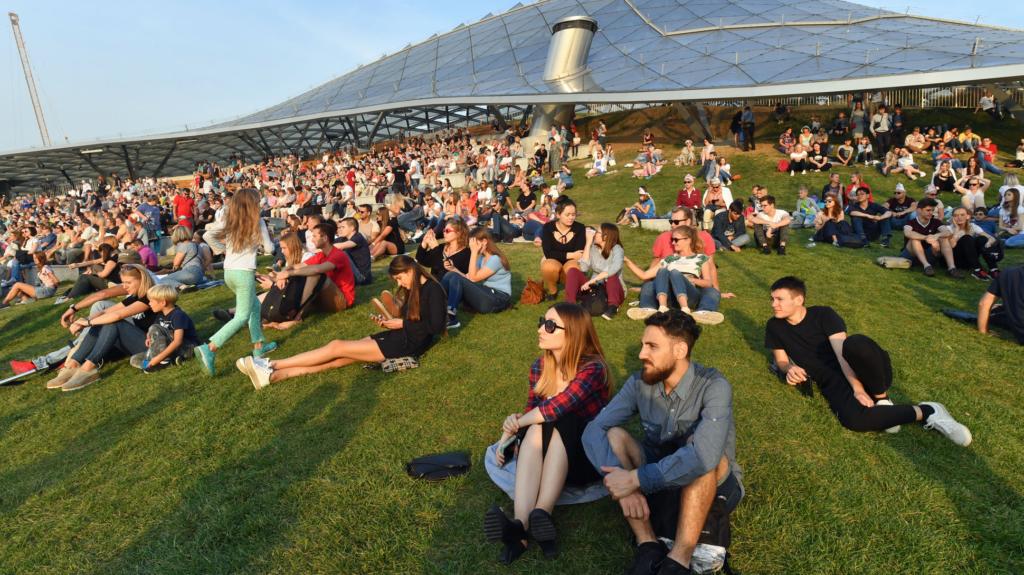 люди сидят на газоне в парке